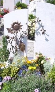 Grab mit Sonnenblume, Rose und Kirschblüten